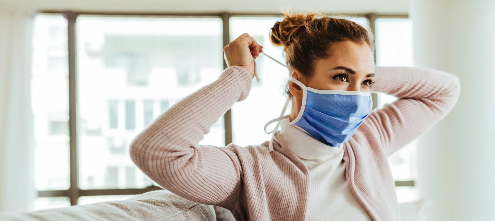 Young woman putting on face mask while being at home during virus epidemic.